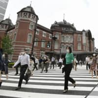 People commute to work near JR Tokyo Station on July 16, a day after Tokyo raised its alert for the novel coronavirus pandemic to the highest level following recent upticks in infections in the capital. | KYODO