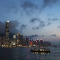 A Star Ferry Co. vessel, owned by Wharf Holdings Ltd., travels across Victoria harbor as Two International Finance Center, left, and other buildings on Hong Kong island stand illuminated at dusk in Hong Kong. | BLOOMBERG