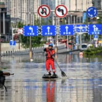 A rescuer paddles across a flooded street in China's southwestern city of Chongqing. | AFP-JIJI