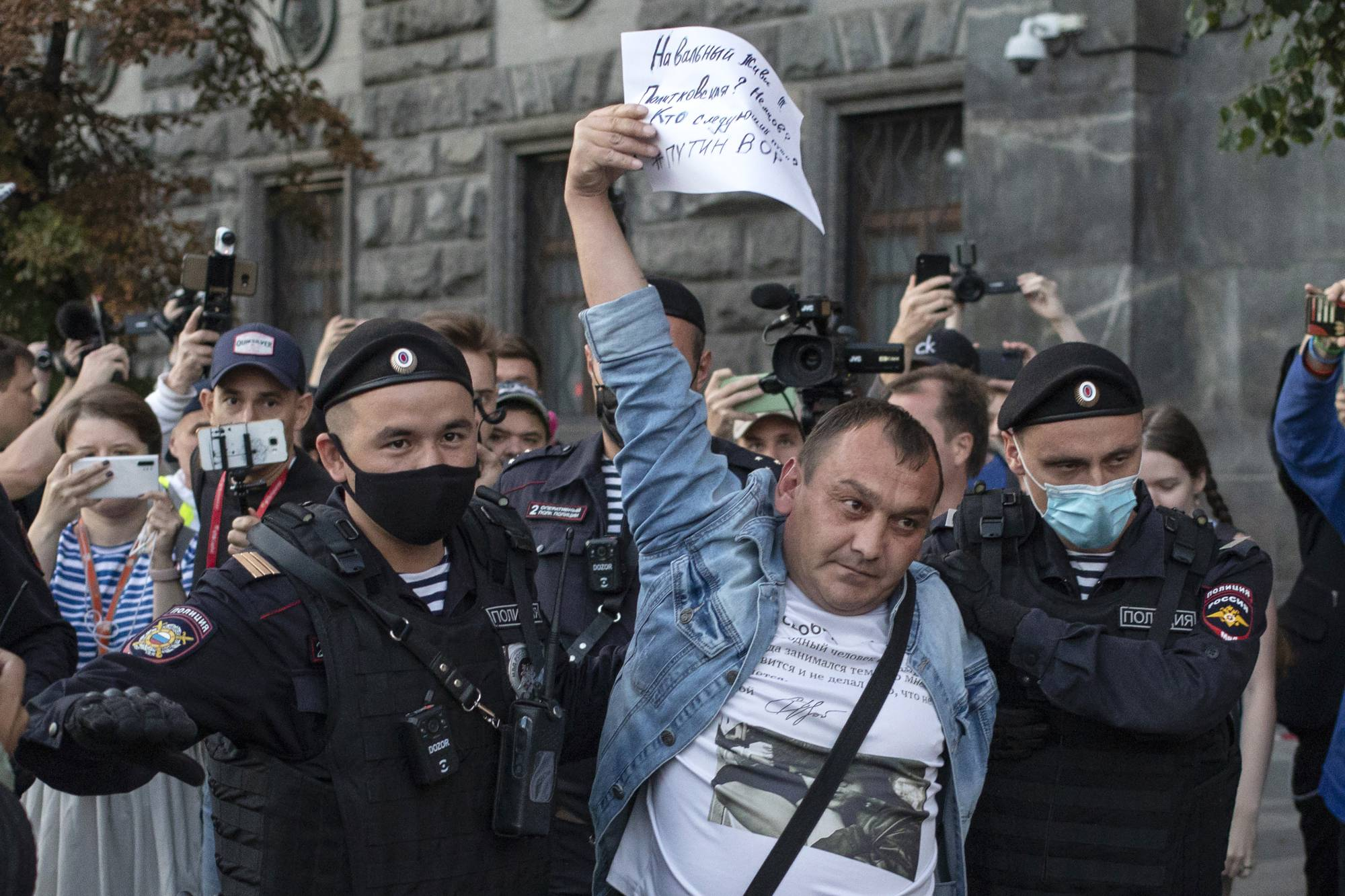 Police officers detain a protester Thursday who supports Russian opposition leader Alexei Navalny in Moscow. | AP
