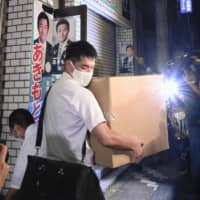 Officials of the Tokyo District Public Prosecutor's Office carry cardboard boxes out of the office of Tsukasa Akimoto in Tokyo's Koto Ward on Thursday. | KYODO