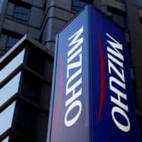 Mizuho Bank announced Friday that people under age 70 who open new bank accounts from Jan. 18 would be charged ¥1,100 if they chose to have a paper passbook. | REUTERS