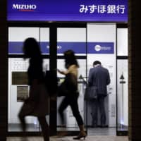 Pedestrians walk past a customer using an automated teller machine at a branch of Mizuho Bank in Tokyo in May. | BLOOMBERG