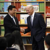 Xi Jinping, China's vice president at the time, shakes hands with U.S. Vice President Joe Biden as they visit a classroom where students are learning Mandarin at the International Studies Learning Center in Los Angeles in February 2012.  | REUTERS