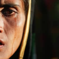 Amina Khatun, a 30-year-old Rohingya refugee who fled with her family from Myanmar a day before, cries after she, along with thousands of newly arrived refugees, spent a night by the road between refugee camps near Cox's Bazar, Bangladesh, in October 2017. | REUTERS
