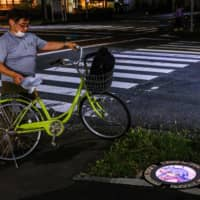 The illuminated manhole covers in Tokorozawa have been met with a positive reception from residents and fans. | AFP-JIJI