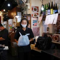 A worker holds a plastic bag containing a take-away lunch at a restaurant in Hong Kong after the government banned dine-in services due to the COVID-19 pandemic. | REUTERS