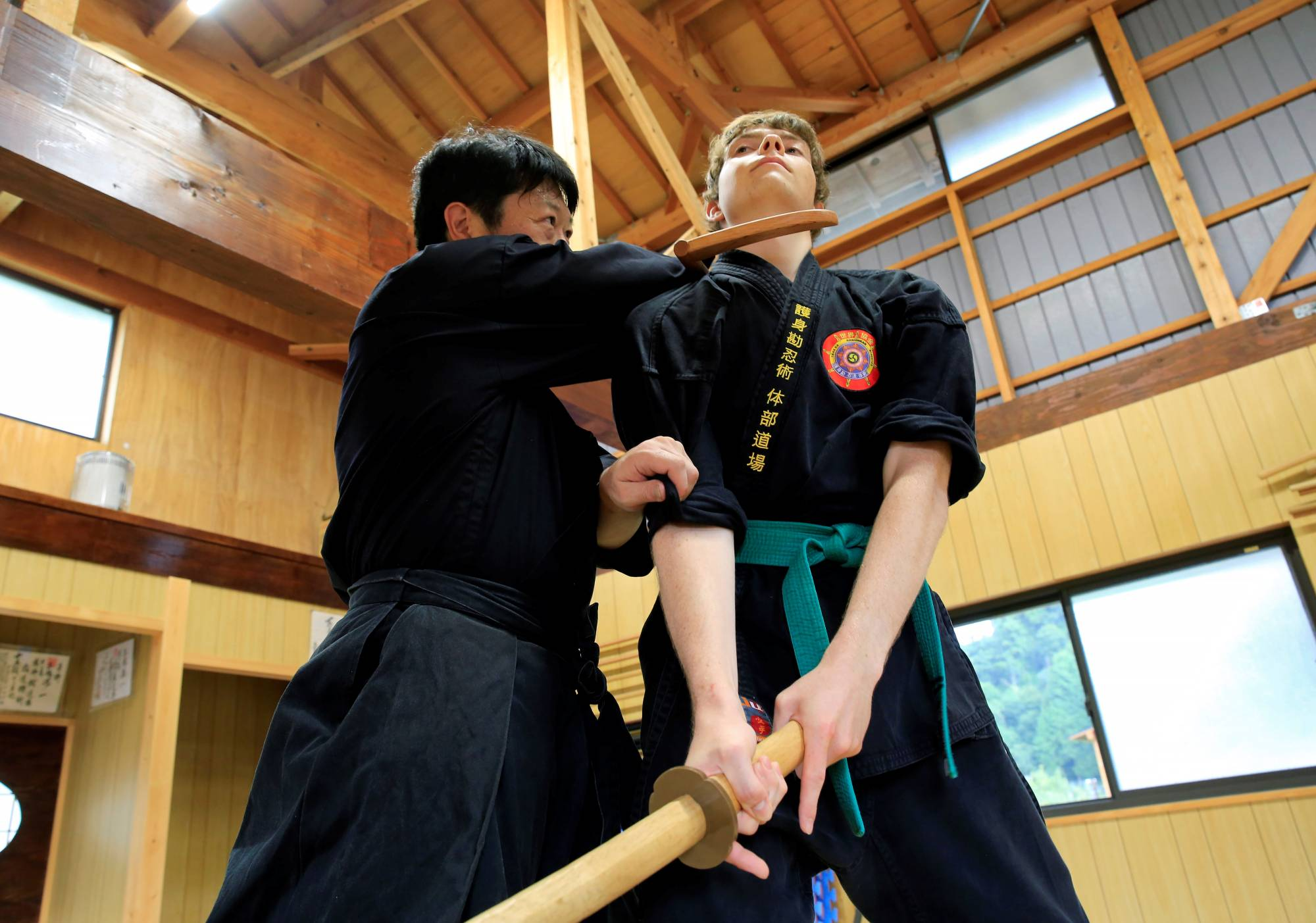 Genichi Mitsuhashi, 45, the first person to hold a degree from Mie University's graduate course on ninja studies, teaches martial arts to a guest in a training hall next to his home in Iga, Mie Prefecture, on July 30. | REUTERS