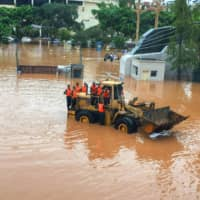 Rescuers prepare to use a loader to evacuate residents at a flooded area in Leshan, Sichuan province, on Tuesday.   | AFP-JIJI