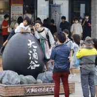 Tourists take a photo in the Owakudani hot spring district of Mount Hakone, a popular tourist spot southwest of Tokyo, on July 23, the first weekend after the Go To Travel campaign was launched. | KYODO