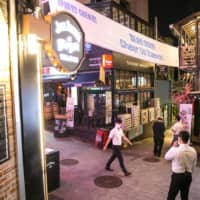 Pedestrians walk through the Itaewon district of Seoul on Friday.  | BLOOMBERG