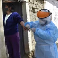 A health worker carries out a COVID-19 test on a woman during an epidemiological sweep in La Paz on Friday, visiting house by house.  | AFP-JIJI