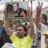 A man holds a poster with a portrait of Alexei Navalny reading 'Navalny was poisoned, we know who is to blame, Alexei you must live' during an unsanctioned protest on Saturday in Khabarovsk, 6,100 kilometers (3,800 miles) east of Moscow. | AP