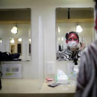 An actor dressed as a zombie puts makeup on before a coffin horror show performed by Kowagarasetai (Scare Squad)  in Tokyo on Aug. 5. | REUTERS