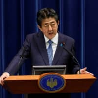 Prime Minister Shinzo Abe speaks at a news conference in Tokyo on June 18. | POOL / VIA REUTERS