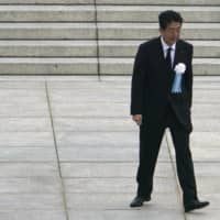 Prime Minister Shinzo Abe walks away after delivering a speech during a ceremony to mark the 75th anniversary of the atomic bombing of Hiroshima at the city's Peace Memorial Park on Aug. 6. | AP