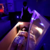 A participant lies inside a mock coffin with plastic shields to maintain social distancing during a coffin horror show performed by Kowagarasetai (Scare Squad) in Tokyo on Saturday. | REUTERS