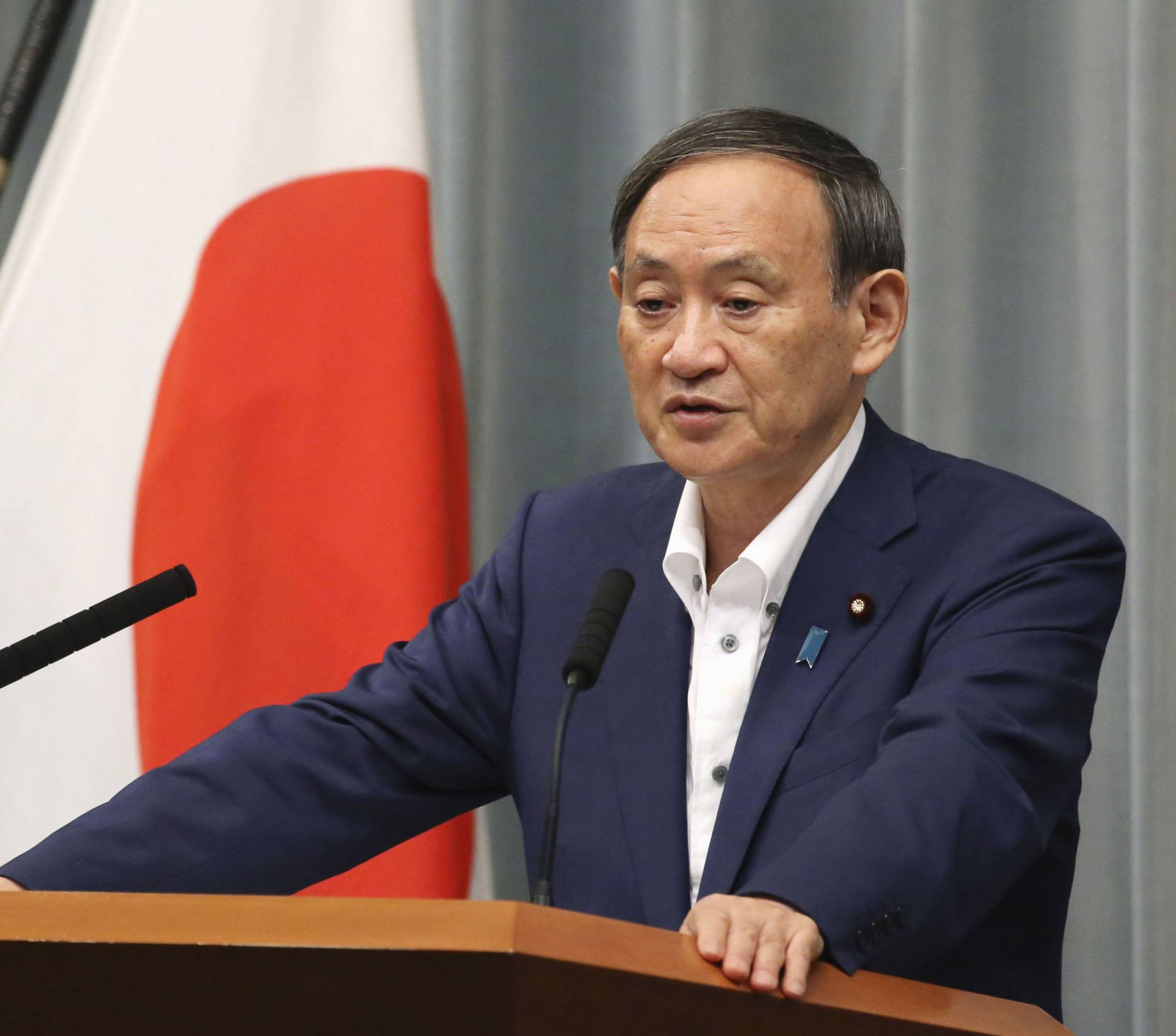 Chief Cabinet Secretary Yoshihide Suga holds a news conference at the Prime Minister's Office on Aug. 11. | KYODO