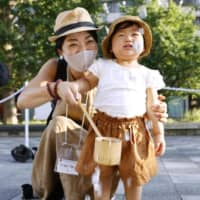 A mother and her child take part in a water-sprinkling event aimed at countering the summer heat in Tokyo on Friday.   KYODO