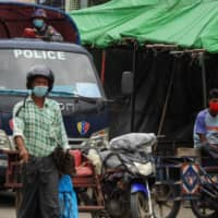A police officer in a vehicle watches over a street Sunday during a lockdown amid fears of the COVID-19 virus in Sittwe, the capital of Rakhine state, in southern Myanmar.  | AFP-JIJI