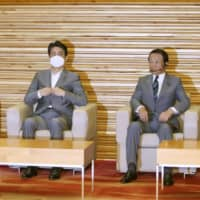 Prime Minister Shinzo Abe attends a Cabinet meeting along with Finance Minister Taro Aso (right) and Foreign Minister Toshimitsu Motegi earlier this month. | KYODO