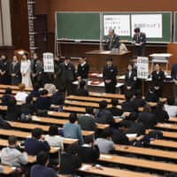 Students take an entrance exam at the University of Tokyo in January. | KYODO