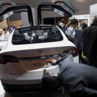 An attendee views a Tesla Model X with a Panasonic battery during the Consumer Electronics Show in Las Vegas. | BLOOMBERG