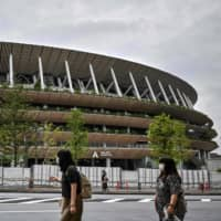 People walk past the National Stadium, the main venue for the 2020 Olympic and Paralympic Games now postponed due to the coronavirus pandemic, in Tokyo on Sunday.   AFP-JIJI