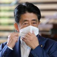 Prime Minister Shinzo Abe prepares to speak to the media on his arrival at the Prime Minister's Office following a visit to a hospital Monday. | AFP-JIJI