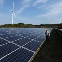 An engineer inspects solar panels at Banpu Power's solar plant in Awaji, Hyogo Prefecture. | BLOOMBERG