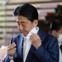 Prime Minister Shinzo Abe takes off his face mask prior to making a short speech to the media upon his arrival at the Prime Minister's Office in Tokyo on Monday. | AFP-JIJI