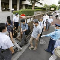 People line up to get seats for the first trial hearing of Katsuyuki Kawai and Anri Kawai at the Tokyo District Court on Tuesday. | KYODO