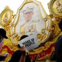 Pro-democracy protesters walk past a picture of Thai King Maha Vajiralongkorn during a rally to demand that the government resign, dissolve the parliament and to hold new elections under a revised constitution, near the Democracy Monument in Bangkok on Aug. 16. | REUTERS