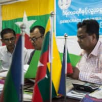 Rohingya candidate Abdul Rasheed (right) and other members of the Democracy and Human Rights Party meet in the party's office in Yangon on Aug. 12. | AFP