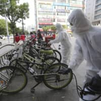 Workers and volunteers disinfect a street in Goyang, South Korea, on Tuesday as a precaution against COVID-19. | AP
