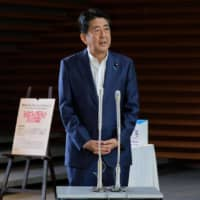 Prime Minister Shinzo Abe speaks to the media upon his arrival at the entrance of the Prime Minister's Office in Tokyo as the 2020 Olympics mascots are seen on Monday. | AFP-JIJI