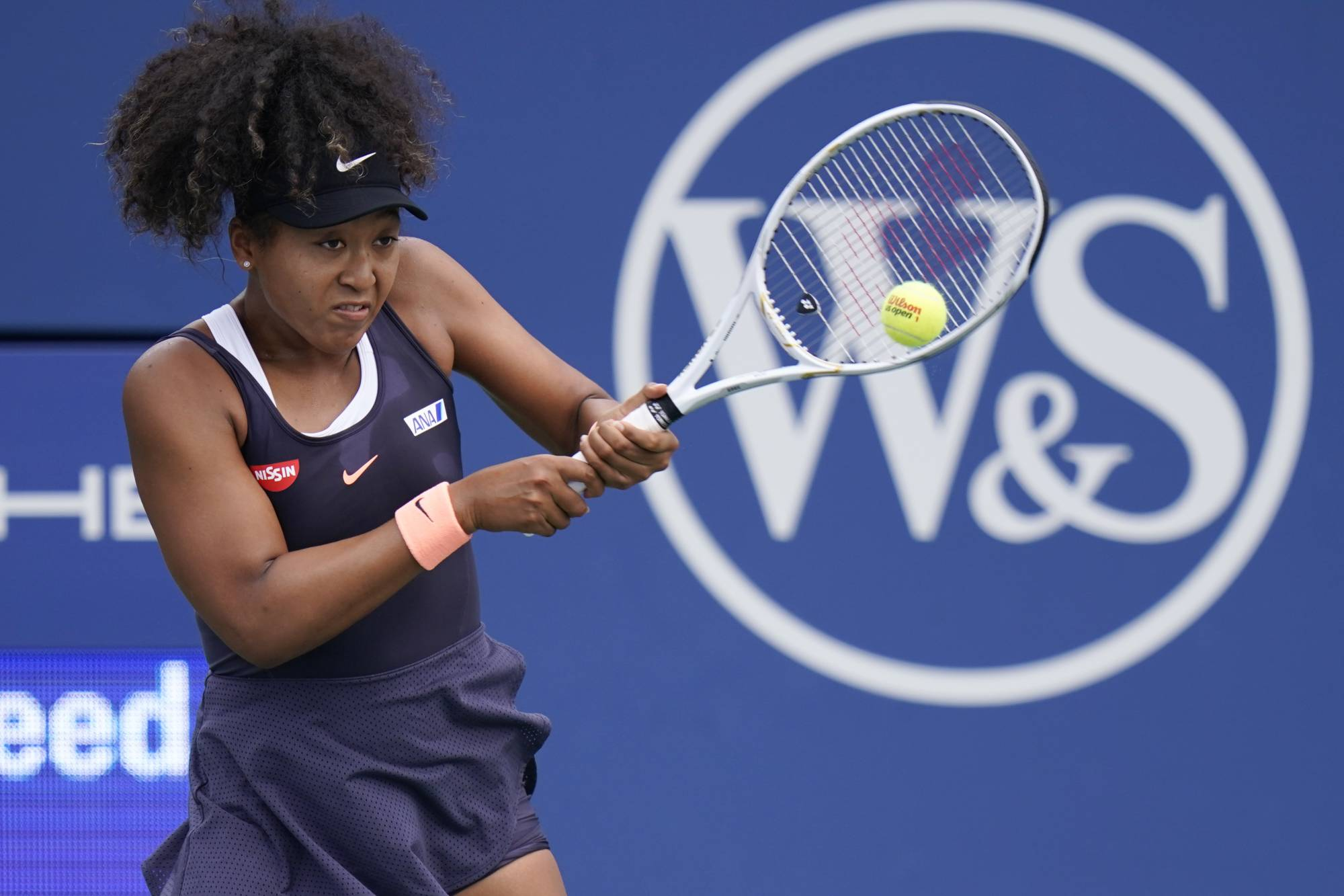 Naomi Osaka hits a return against Dayana Yastremska, of Ukraine, during the third round of the Western and Southern Open in New York on Tuesday. | AP