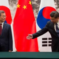Chinese President Xi Jinping gestures toward South Korean President Moon Jae-In during a signing ceremony at the Great Hall of the People in Beijing, in December 2017. South Korea is caught between maintaining strong ties with China — its biggest trading partner — and the U.S., its main military ally and a key market for the exports that power its economy.  | REUTERS