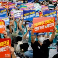 Medical residents and doctors hold up signs during a strike in Seoul on Aug. 14.  | REUTERS