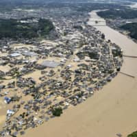 The city of Hitoyoshi, Kumamoto Prefecture, is seen flooded in July after the Kuma River overflowed due to torrential rain. | KYODO