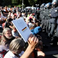 A protester in Berlin holds a copy of the German constitution during a rally Aug. 1 against the government's restrictions over the coronavirus outbreak. | REUTERS