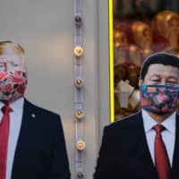 Cardboard cutouts of images of U.S. President Donald Trump and Chinese leader Xi Jinping adorned with protective masks are displayed in Moscow in March. | REUTERS