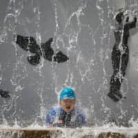 A child cools off under a public fountain during hot summer weather at a park in Tokyo on Aug. 13.  | REUTERS