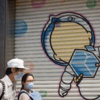 Pedestrians wearing protective masks walk past a mural on a store shutter in Sapporo on Aug. 19 . | BLOOMBERG