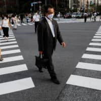 People wearing protective masks make their way amid the coronavirus pandemic in a business district in Tokyo in early August.  | REUTERS