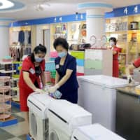 Employees spray sanitizer on items at a store in Pyongyang. | KCNA / KNS / VIA AFP-JIJI