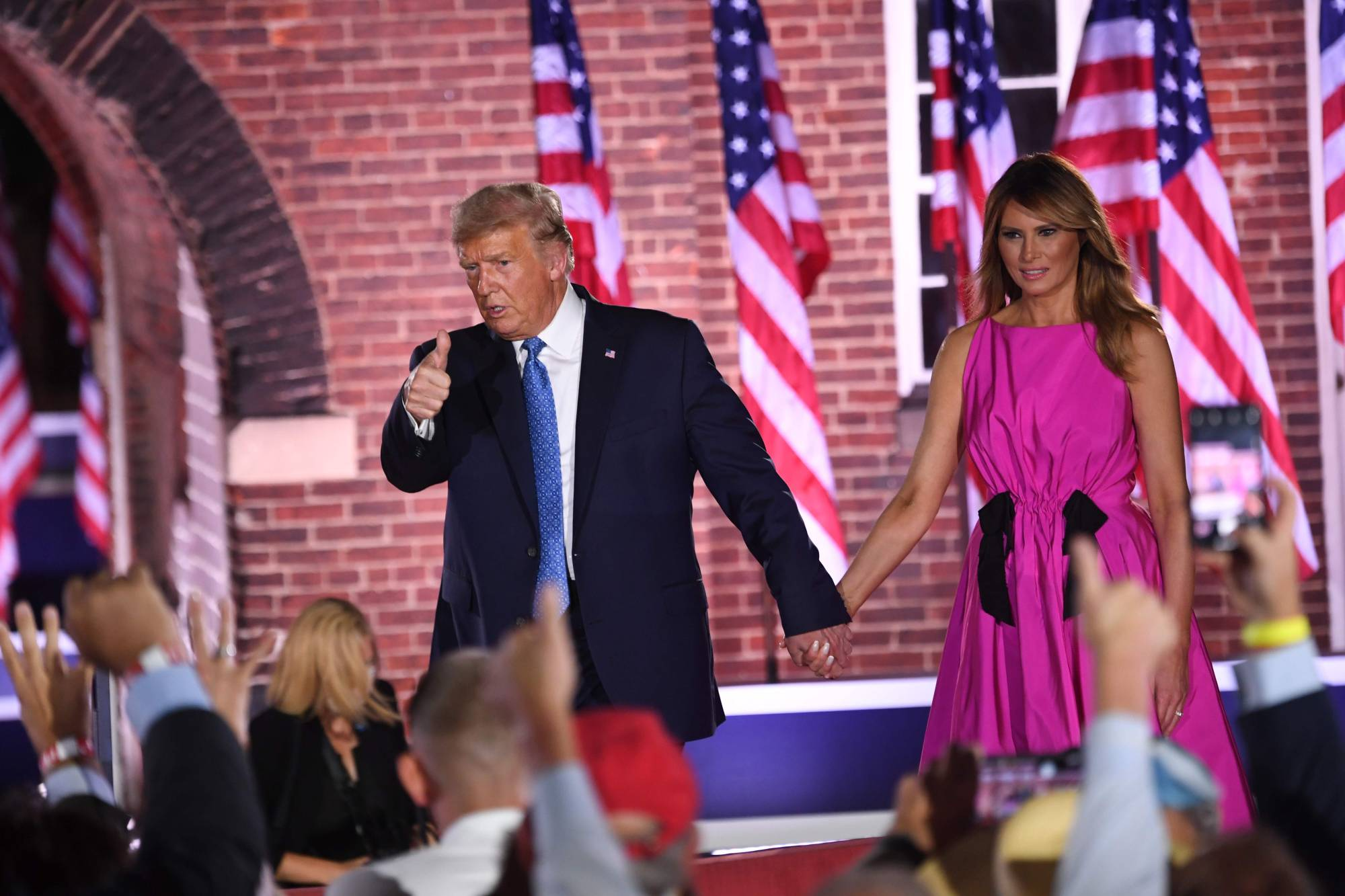 U.S. President Donald Trump holds hands with first lady Melania Trump at the conclusion of the third night of the Republican National Convention on Wednesday. | AFP-JIJI