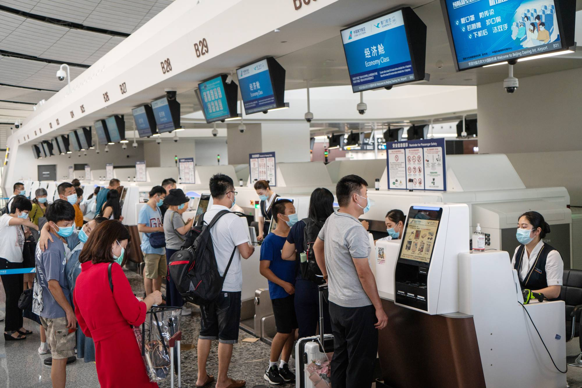 Travelers stand at China Southern Airlines check-in counters at Beijing Daxing International Airport on Tuesday. | BLOOMBERG