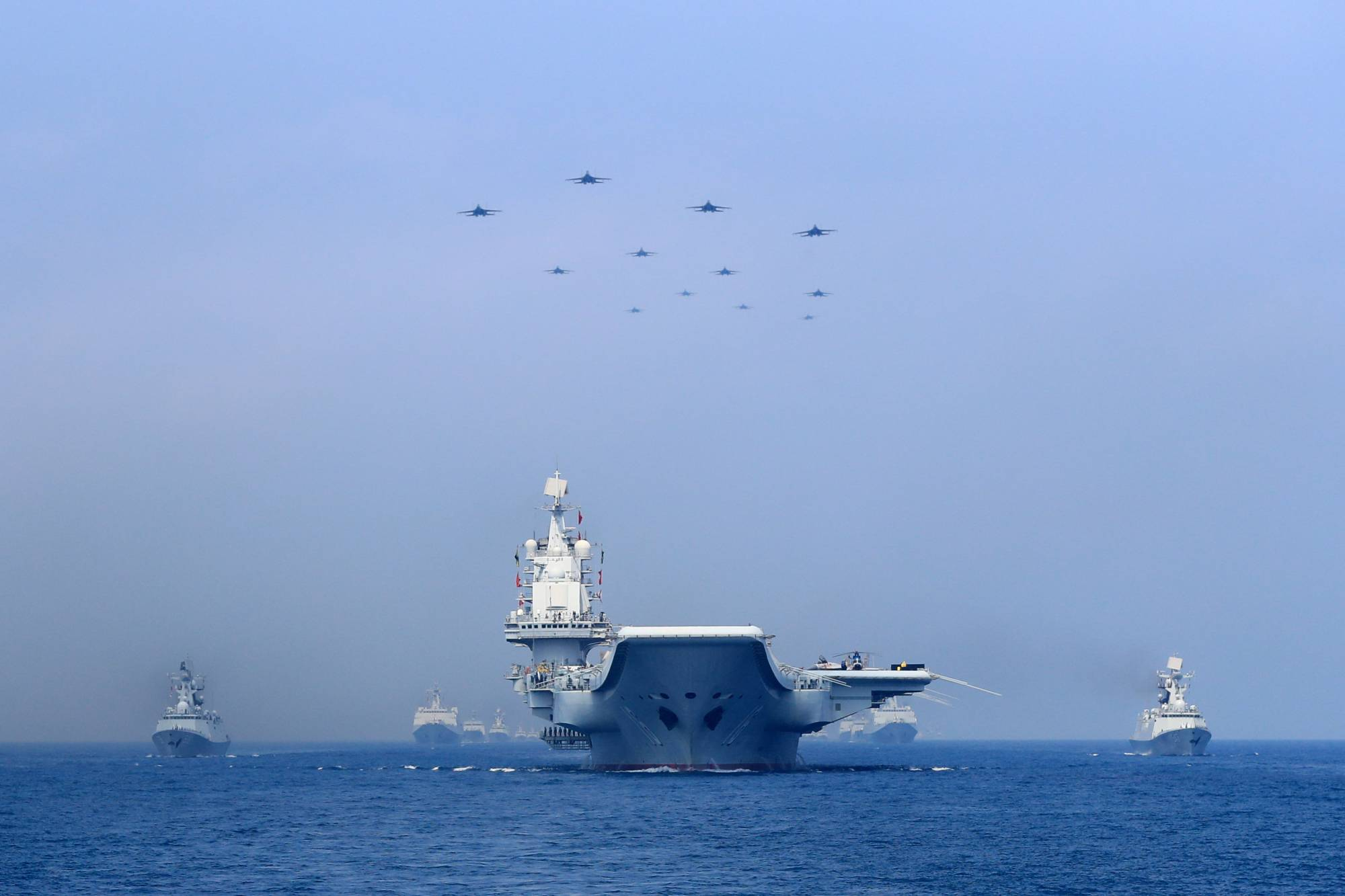 Warships and fighter jets of Chinese People's Liberation Army (PLA) Navy take part in a military display in the South China Sea in April 2018. | REUTERS