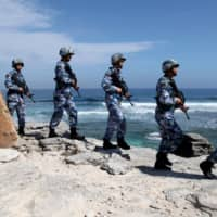 China's People's Liberation Army (PLA) Navy soldiers patrol at Woody Island in the Paracel chain of the South China Sea in January 2016.  | REUTERS